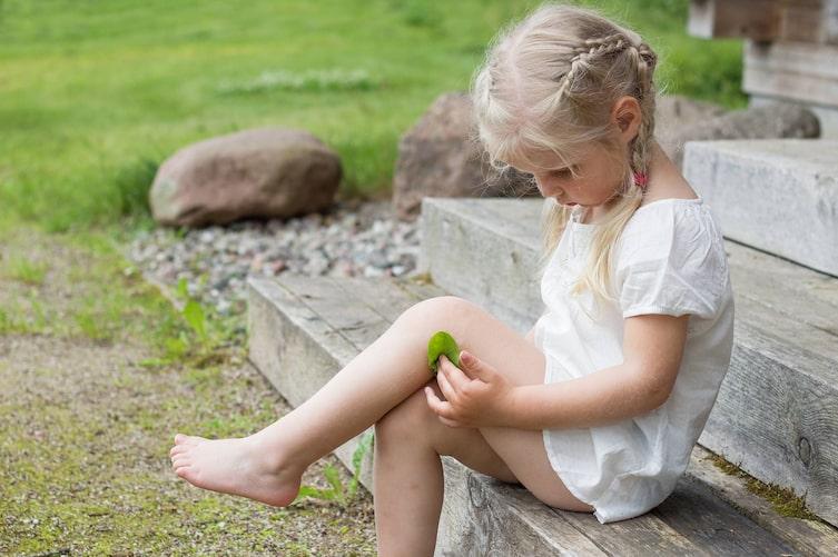 Kind legt Blatt auf Wunde (Bild: Getty Images)