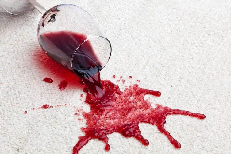 Ein umgefallenes Glas mit Rotwein verschmutzt einen Teppichboden. (Bild: Mauritius Images)