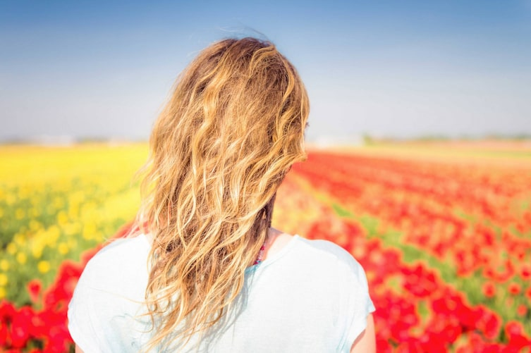 Blonde Frau schaut auf blühendes Mohnfeld. (Bild: Getty Images)